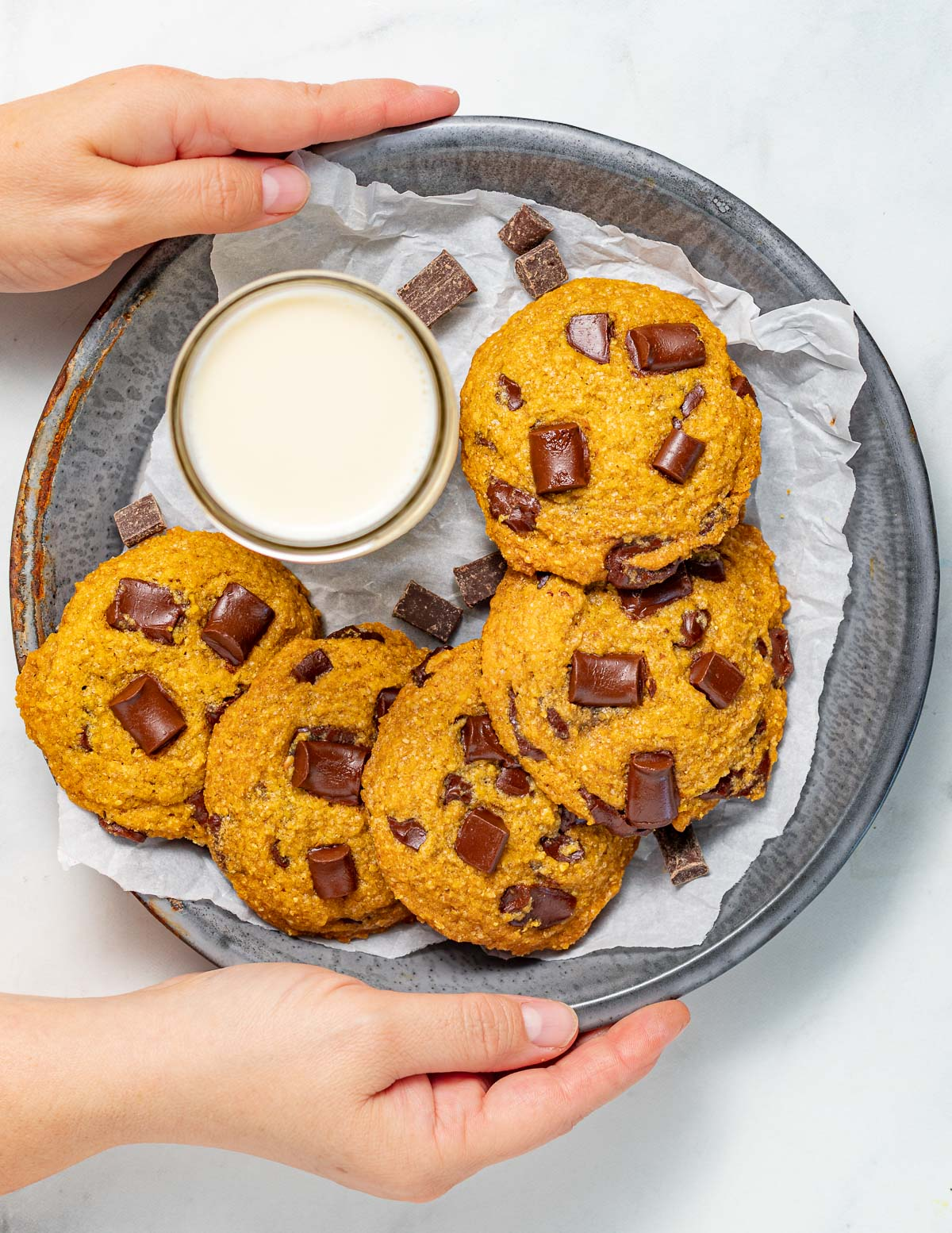 vegan pumpkin chocolate chip cookies on a tray with a glass of soy milk