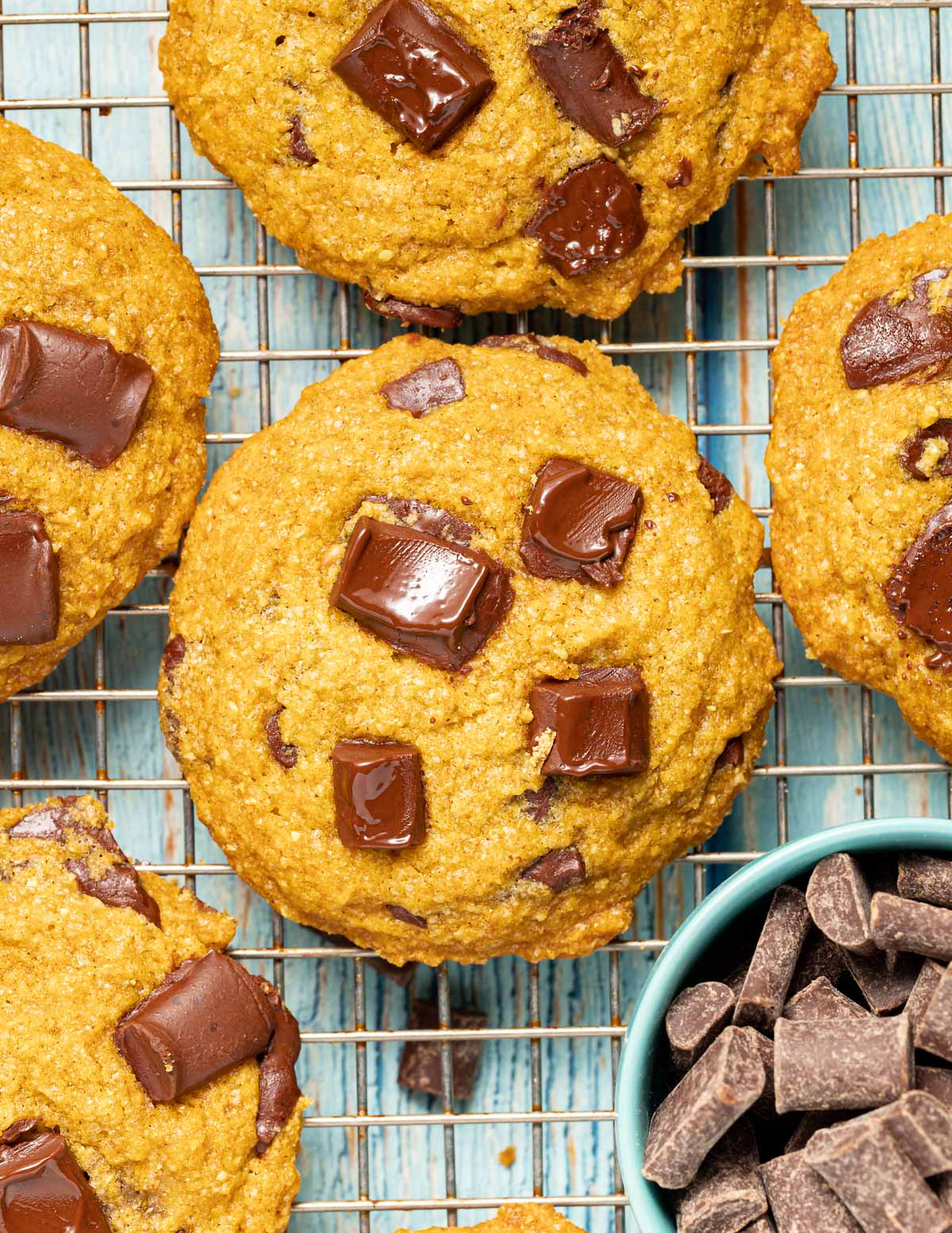 cookies on a cooling rack with a bowl of chocolate chunks