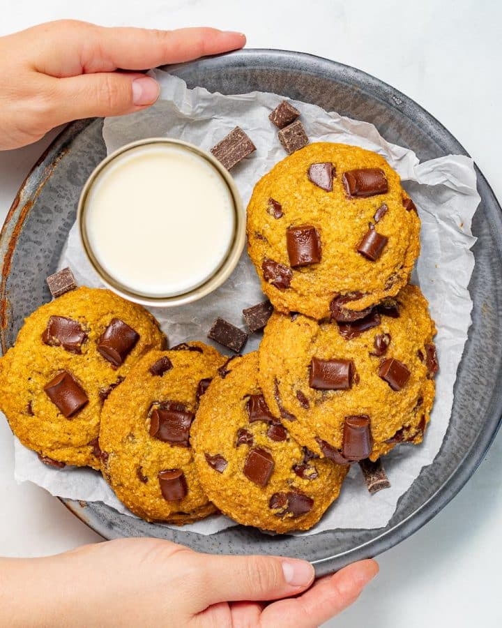 vegan pumpkin chocolate chip cookies on a tray with a glass of milk