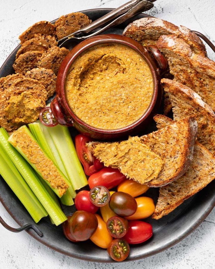 a tray of vegetable pate, toast, crackers, celery and tomatoes