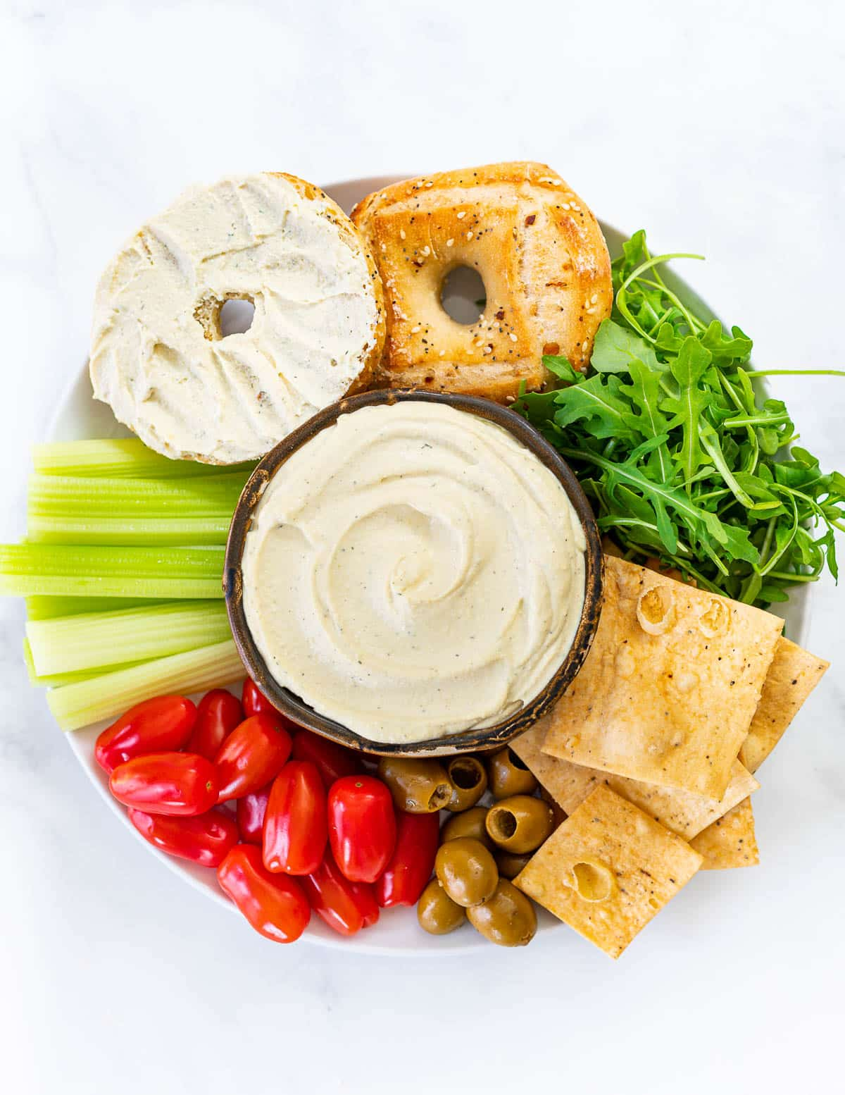 a platter with a bowl of vegan cream cheese, bagels, crackers and vegetables