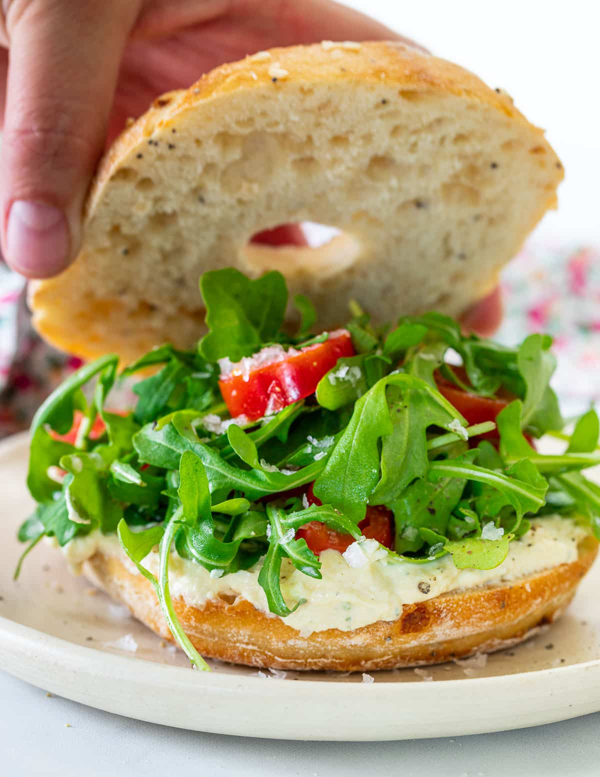 a bagel filled with vegan cream cheese, arugula and tomato