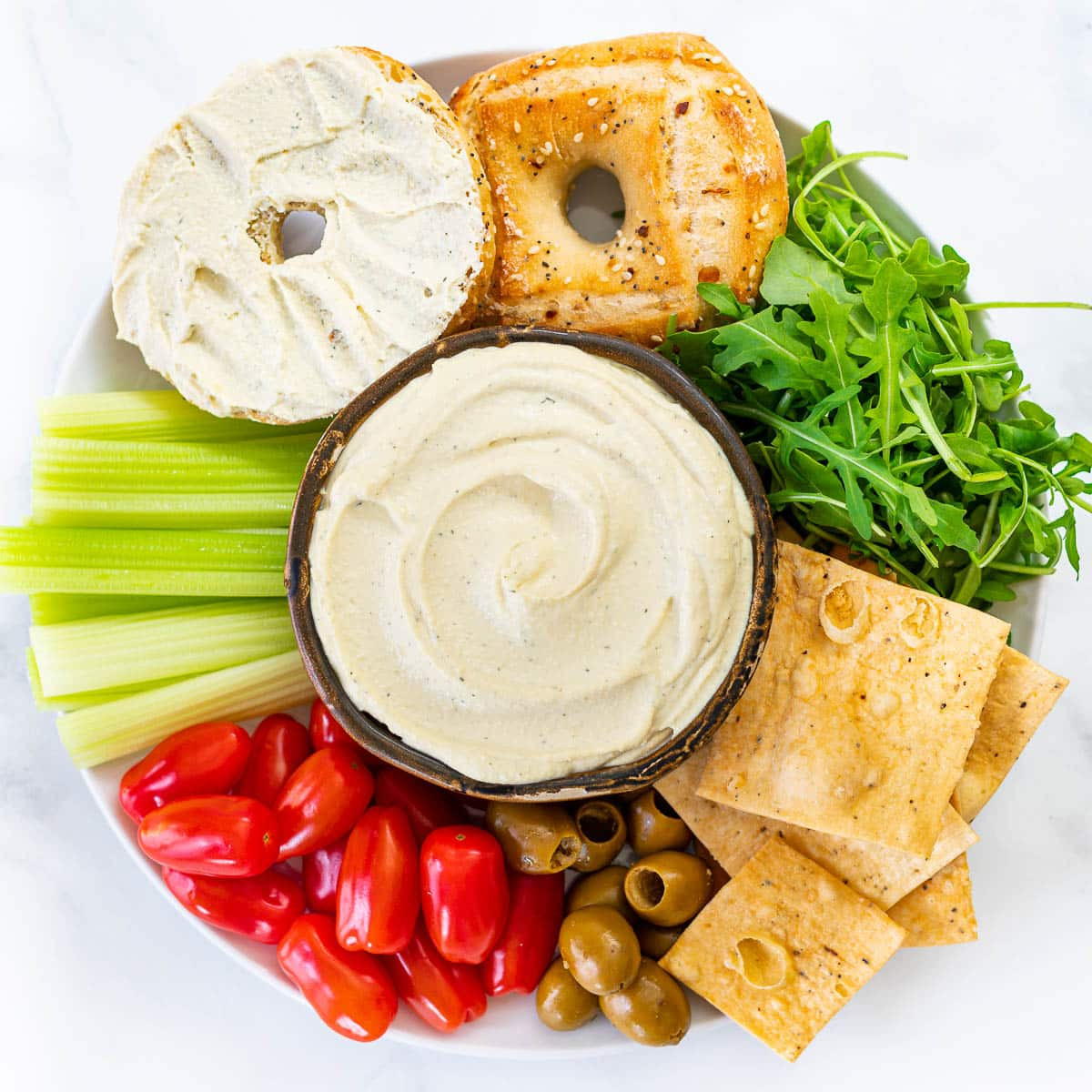 vegan cream cheese on a platter of crackers, bagels, veggies