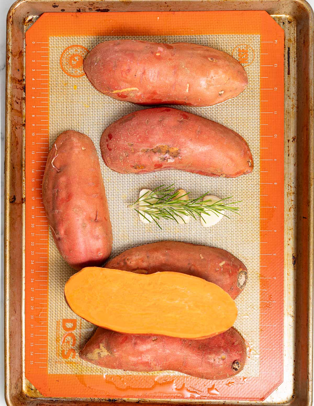 halfed sweet potatoe son a tray with rosemary and garlic
