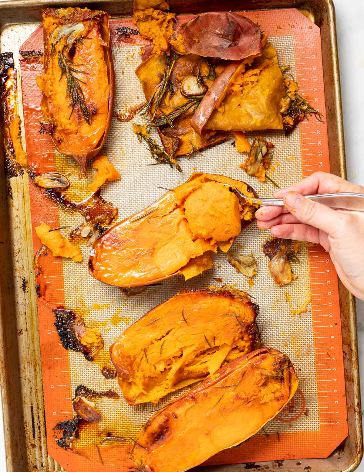 roasted sweet potatoes with garlic and rosemary on a baking tray