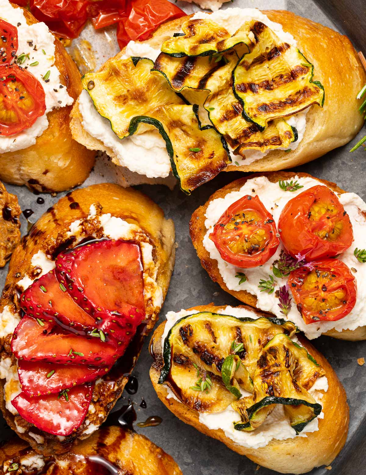 bruschetta topped with tomatoes, zucchini and strawberries