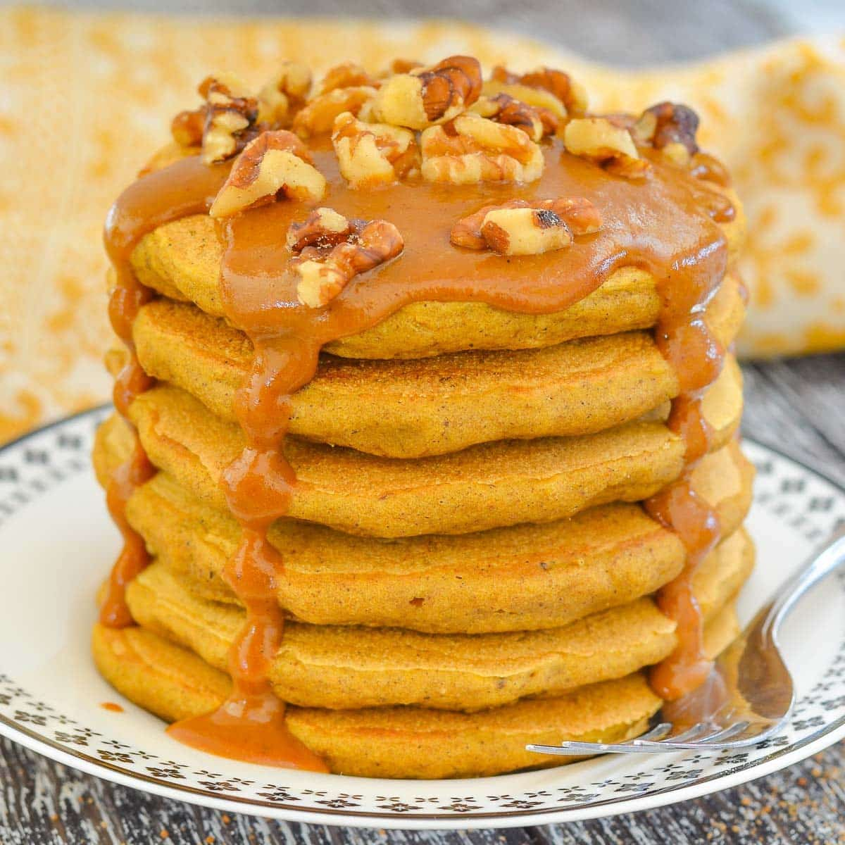 a stack of sweet potato pancakes with caramel and nuts