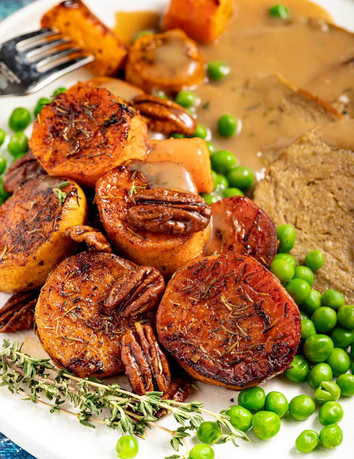 sweet potatoes with pecan nuts on a plate with peas