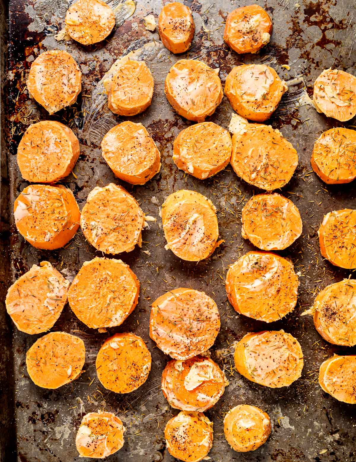 a tray of raw sweet potato rounds coated in vegan butter, herbs and seasoning