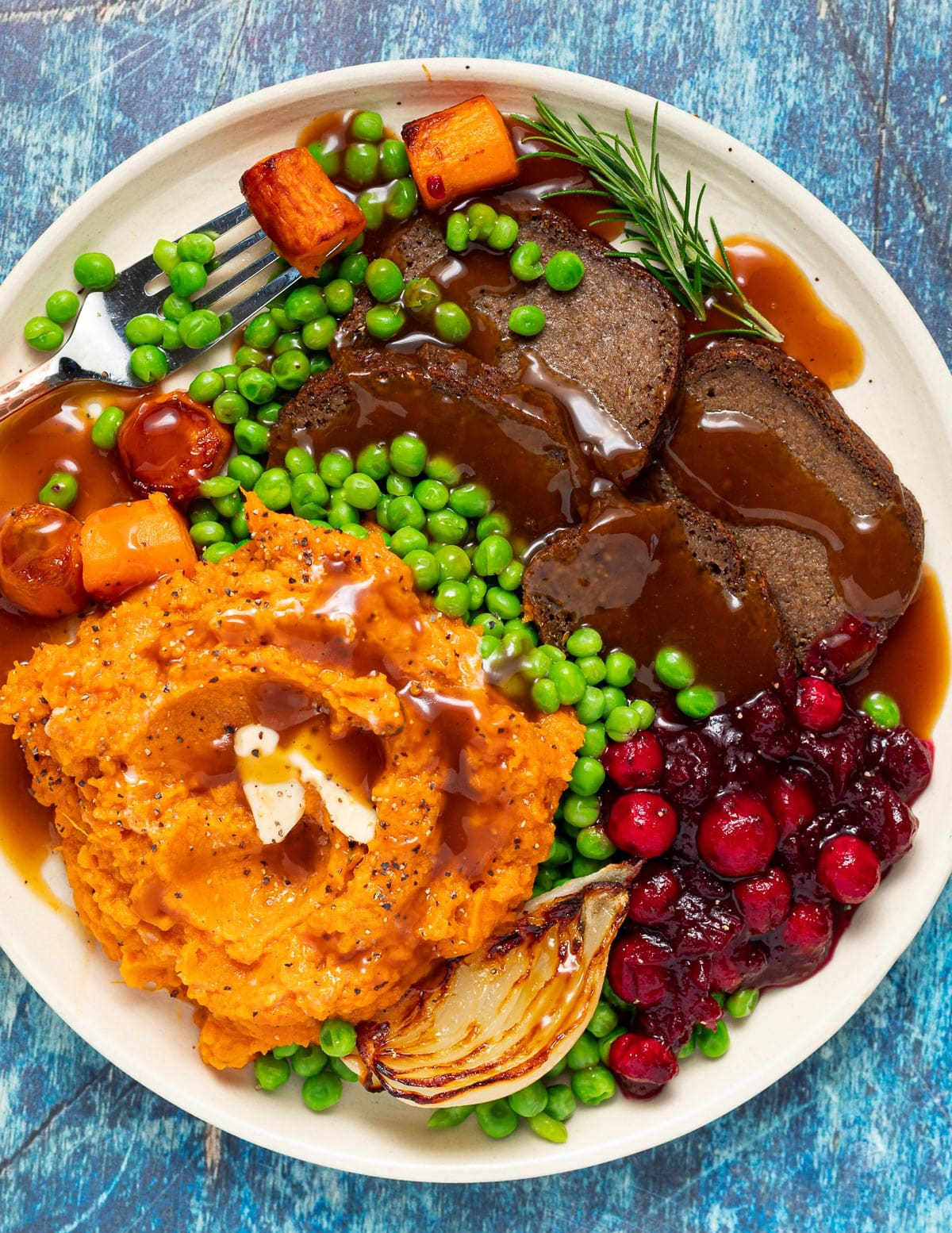 a plate of gluten-free seitan, mashed sweet potato, gravy and vegetables
