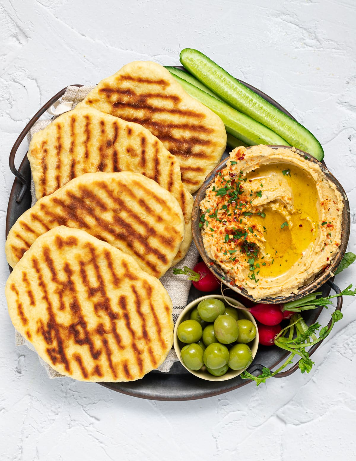 a platter with flatbreads, hummus and veggies