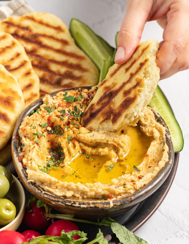 flatbread dipping in hummus