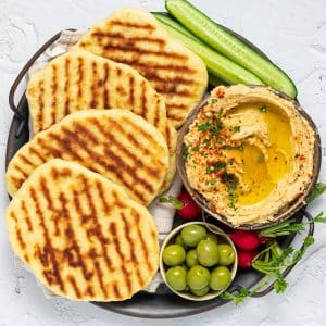 flatbreads on a platter with dip, olives and celery