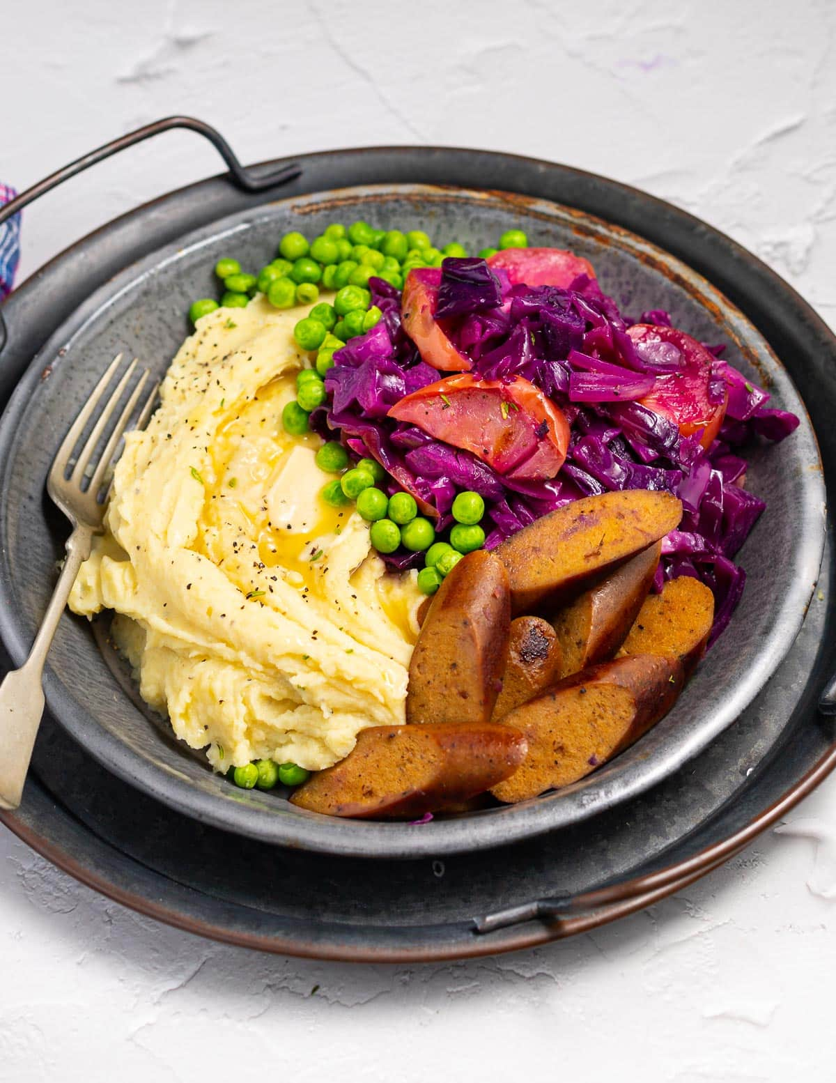 red cabbage, mashed potato and sausages on a metal plate