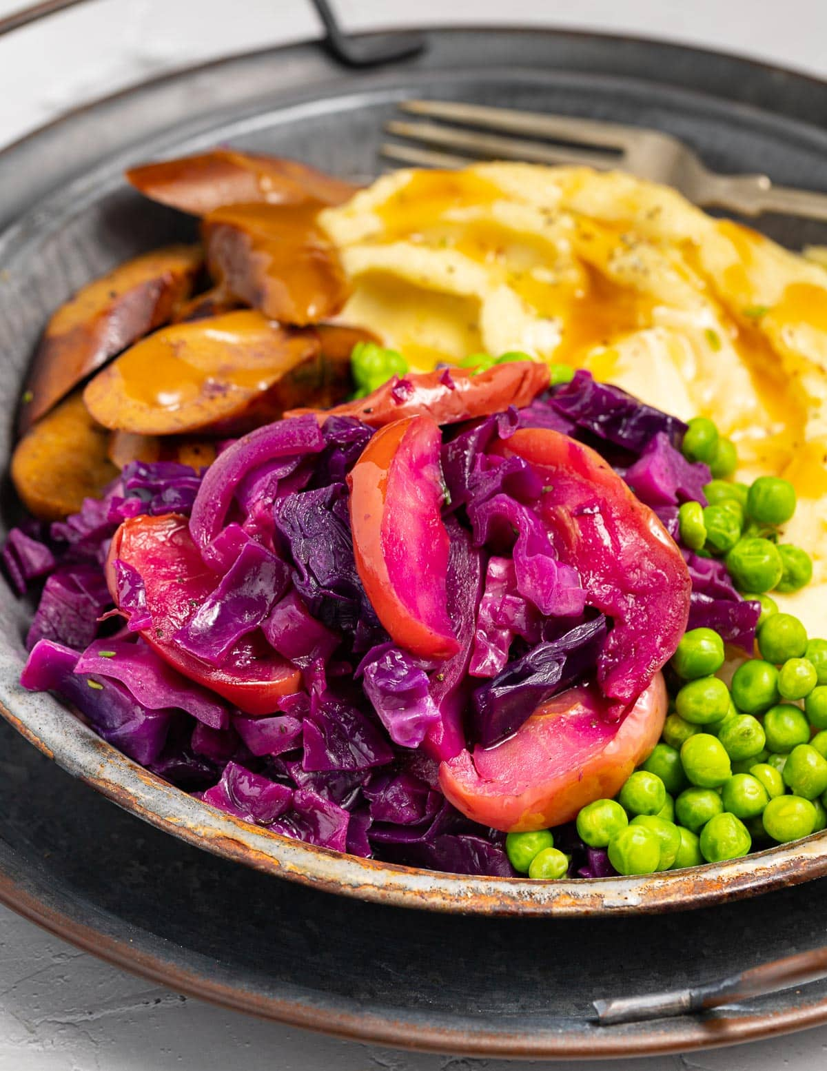 roasted red cabbage and apples with sausage and mashed potato