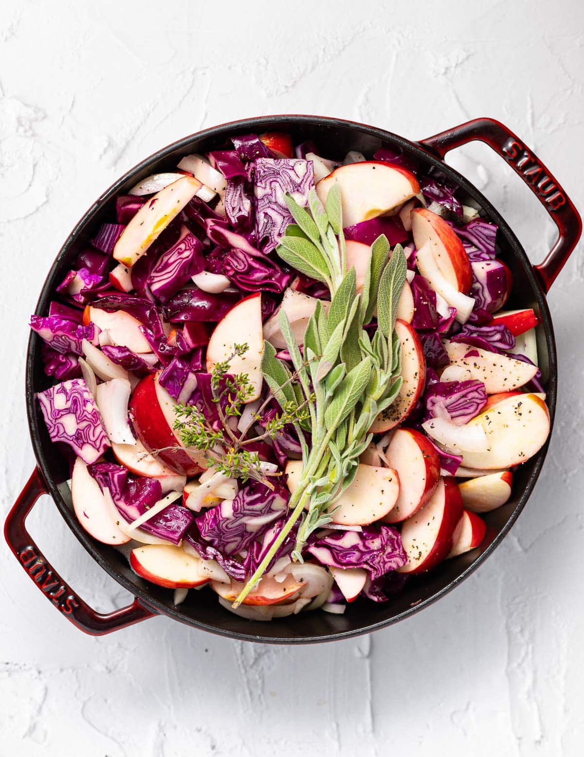 red cabbage, apples and herbs in a skillet