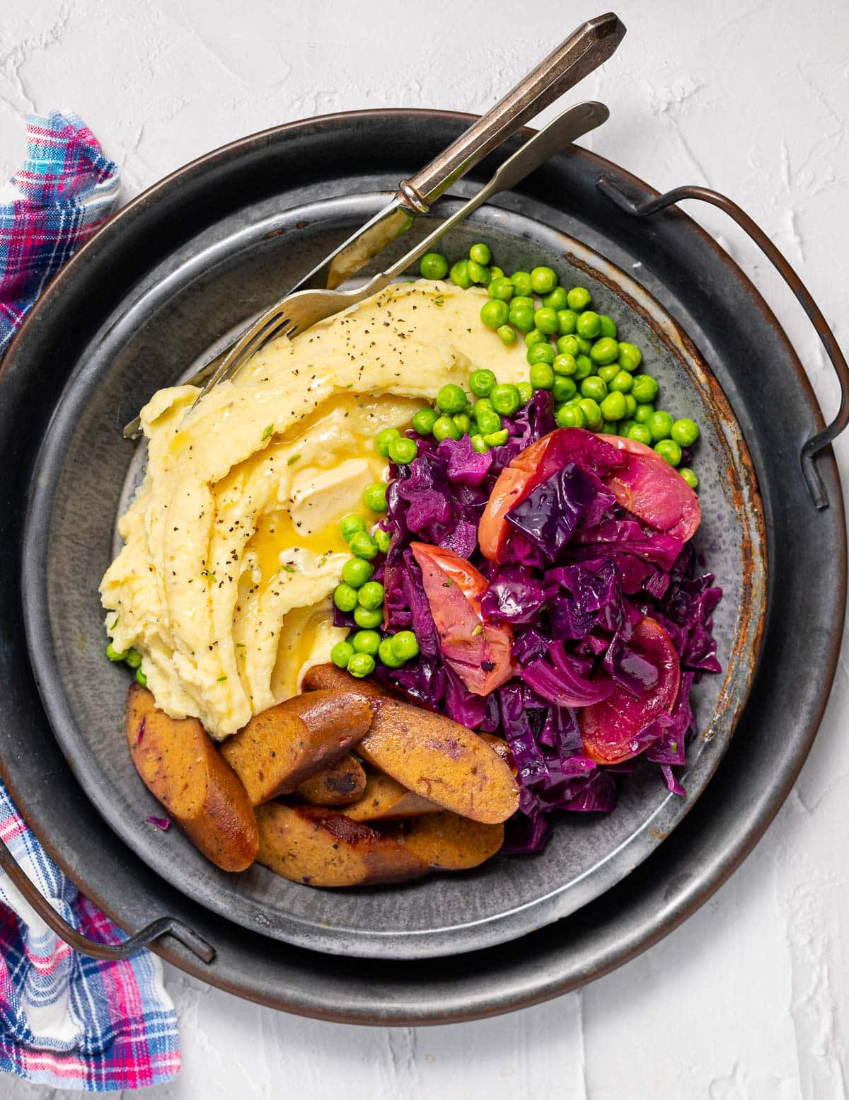 a plate of mashed potato, sausage, red cabbage and peas