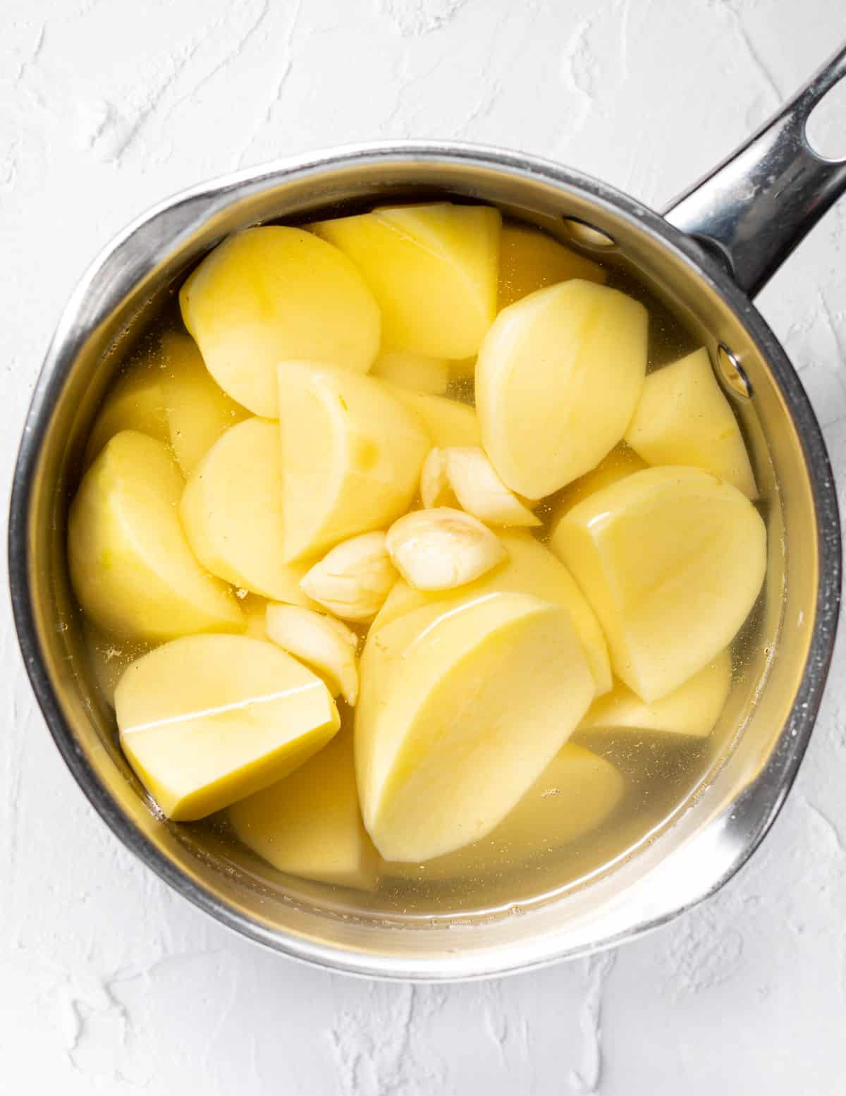 potatoes and garlic in a pan of water