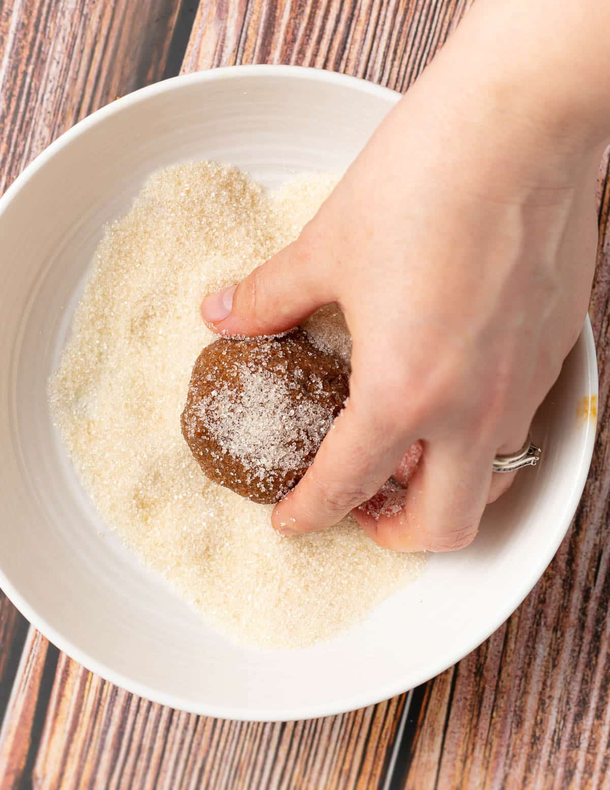 a cookie dough ball being rolled in sugar