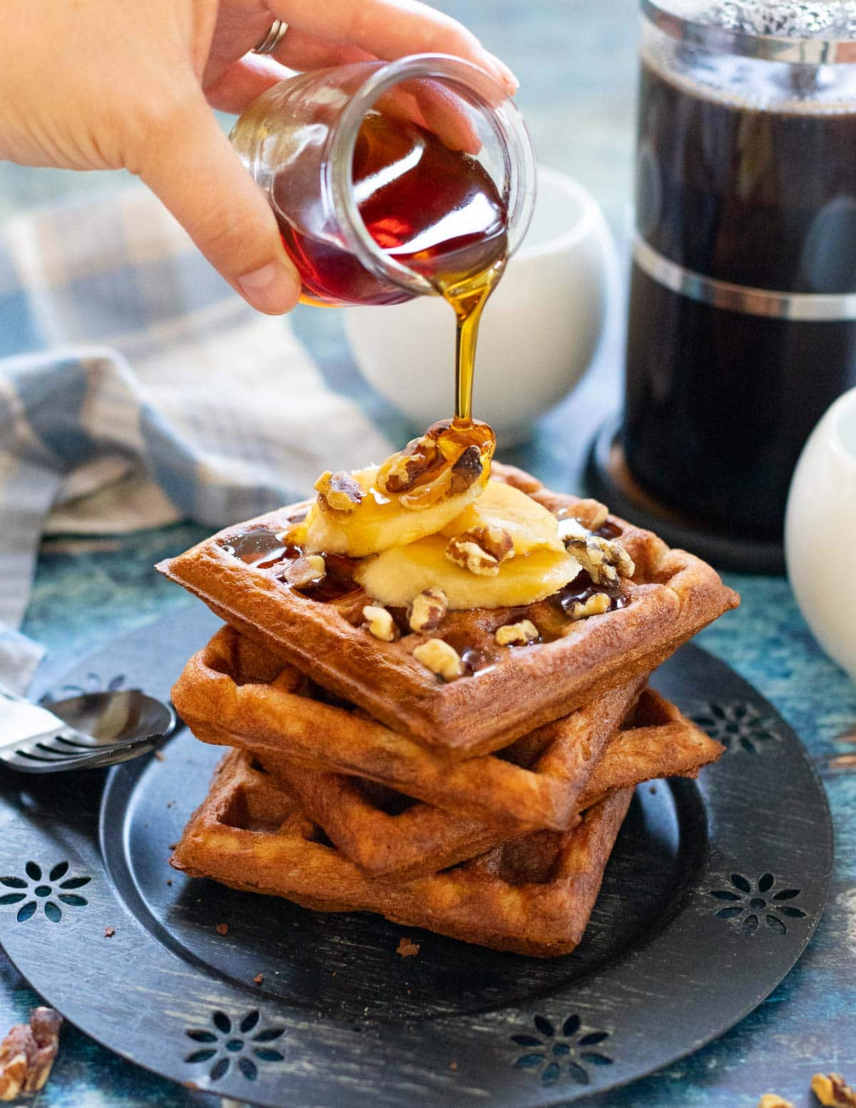 maple syrup pouring over a stack of vegan banana waffles