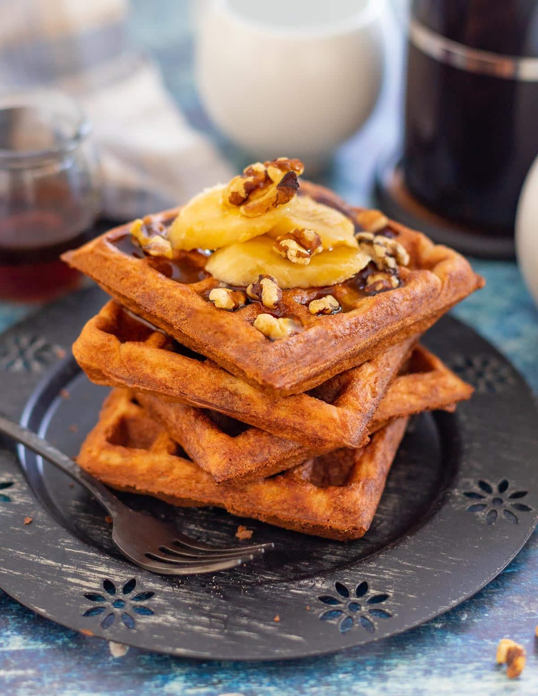 banana waffles topped with banana, nuts and syrup