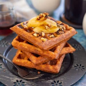 a stack of waffles topped with banana and nuts