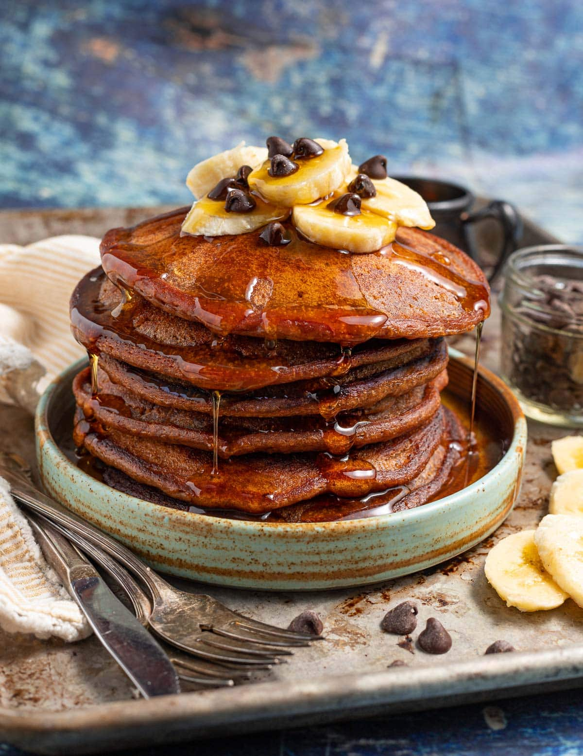 a stack of chocolate banana pancakes with maple syrup