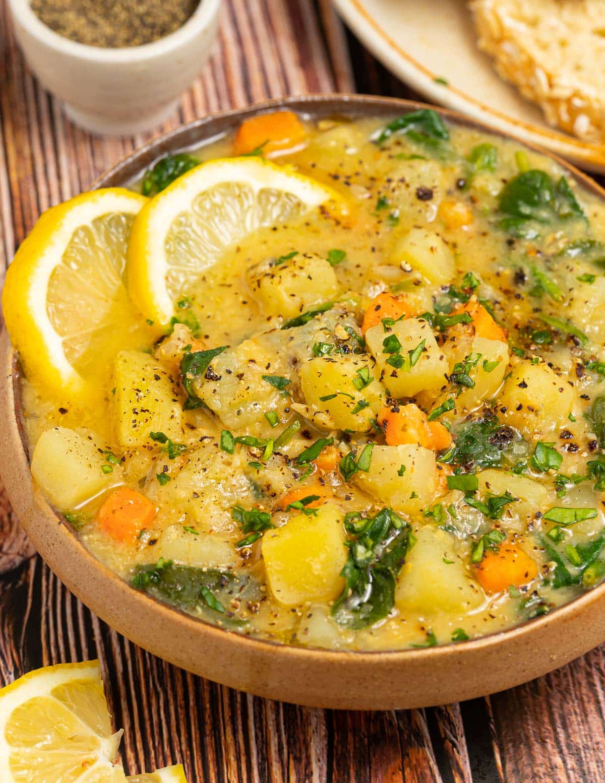 close up of a bowl of red lentil soup with lemon slice garnish
