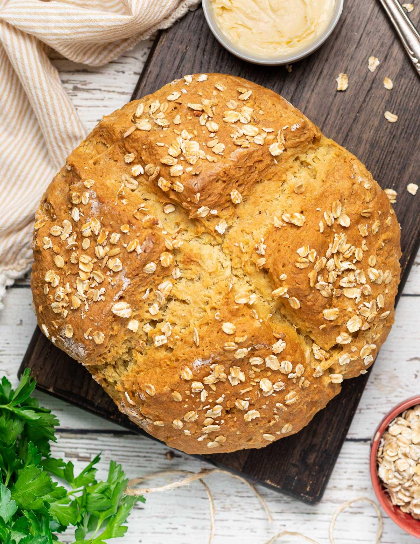 a golden loaf of oat sprinkled soda bread