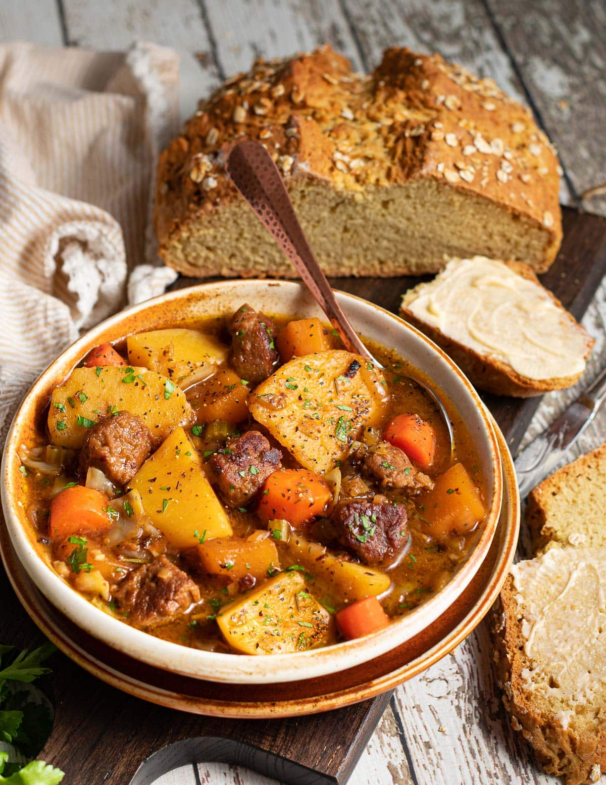 a bowl of stew next to some soda bread