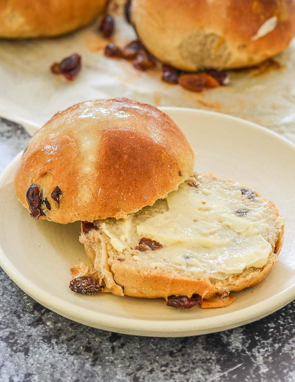 a cut hot cross bun spread with vegan butter