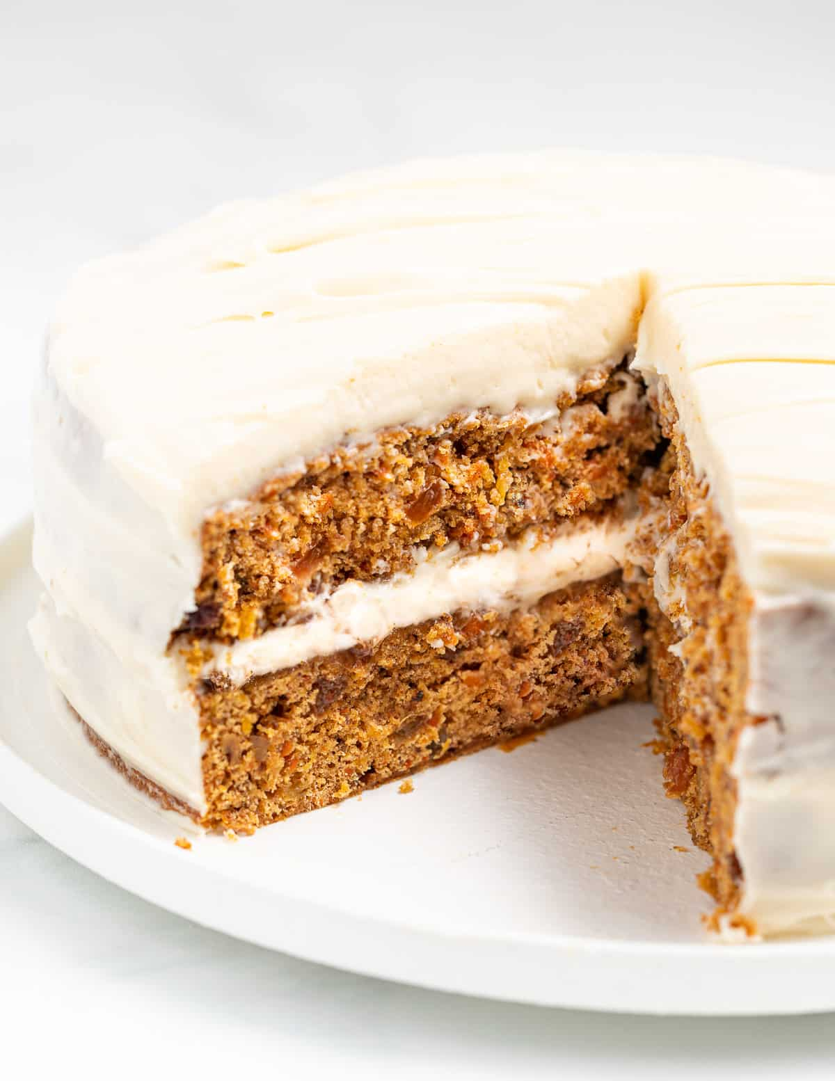 a carrot cake with a big slice taken out so inside is visible