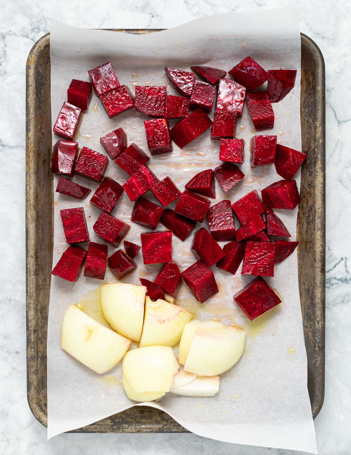 beets and onion on a baking tray