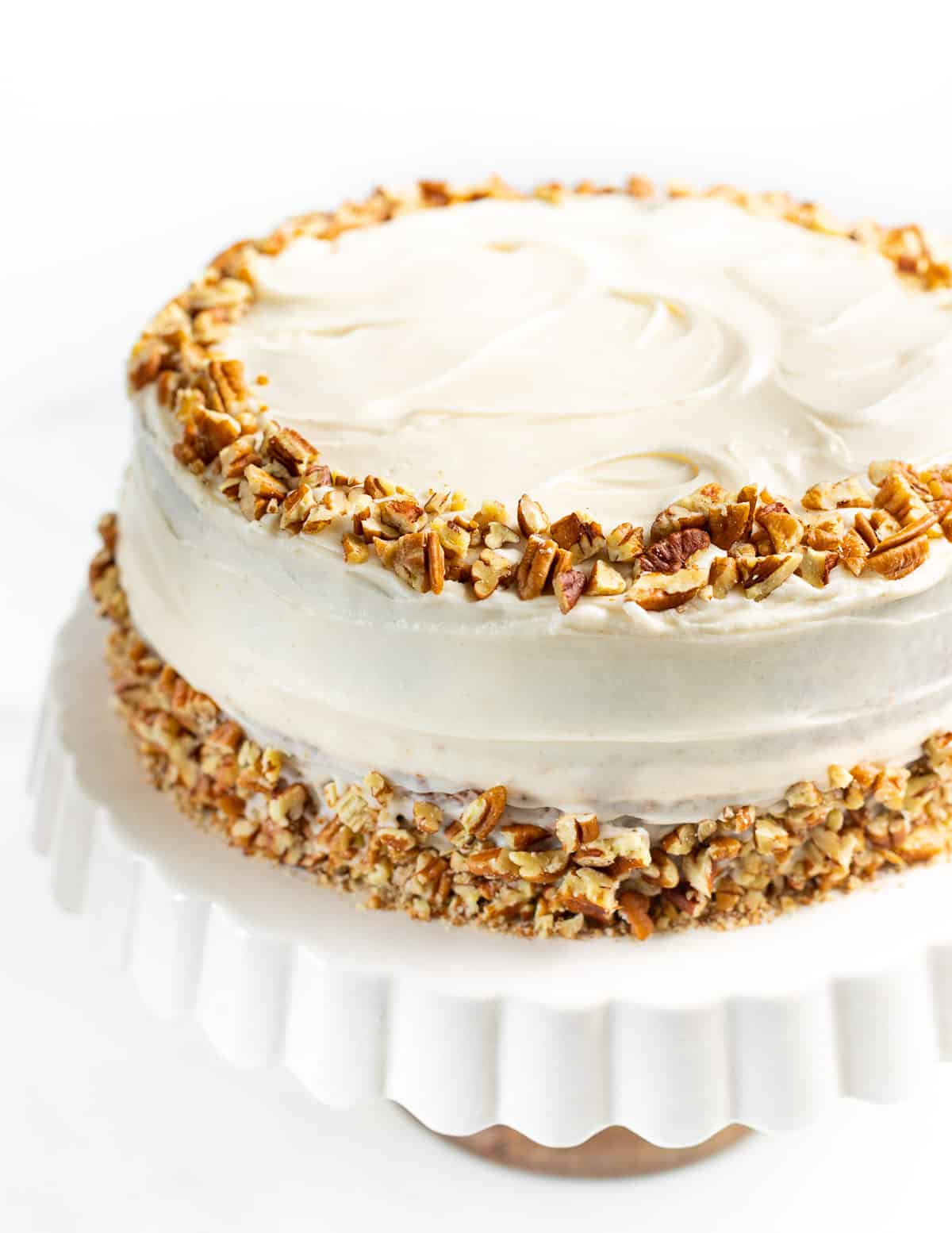 a large vegan hummingbird cake decorated with cream cheese frosting and pecans