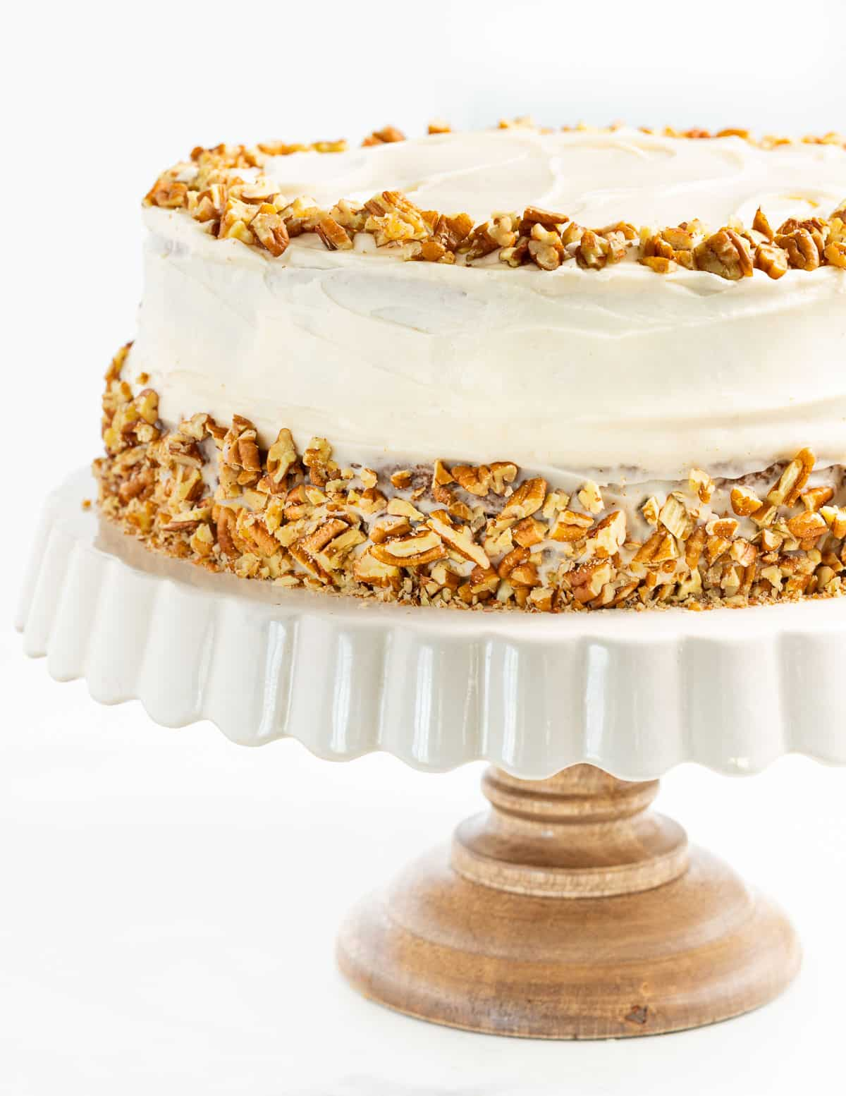 a vegan hummingbird cake decorated with cream cheese frosting and chopped pecans