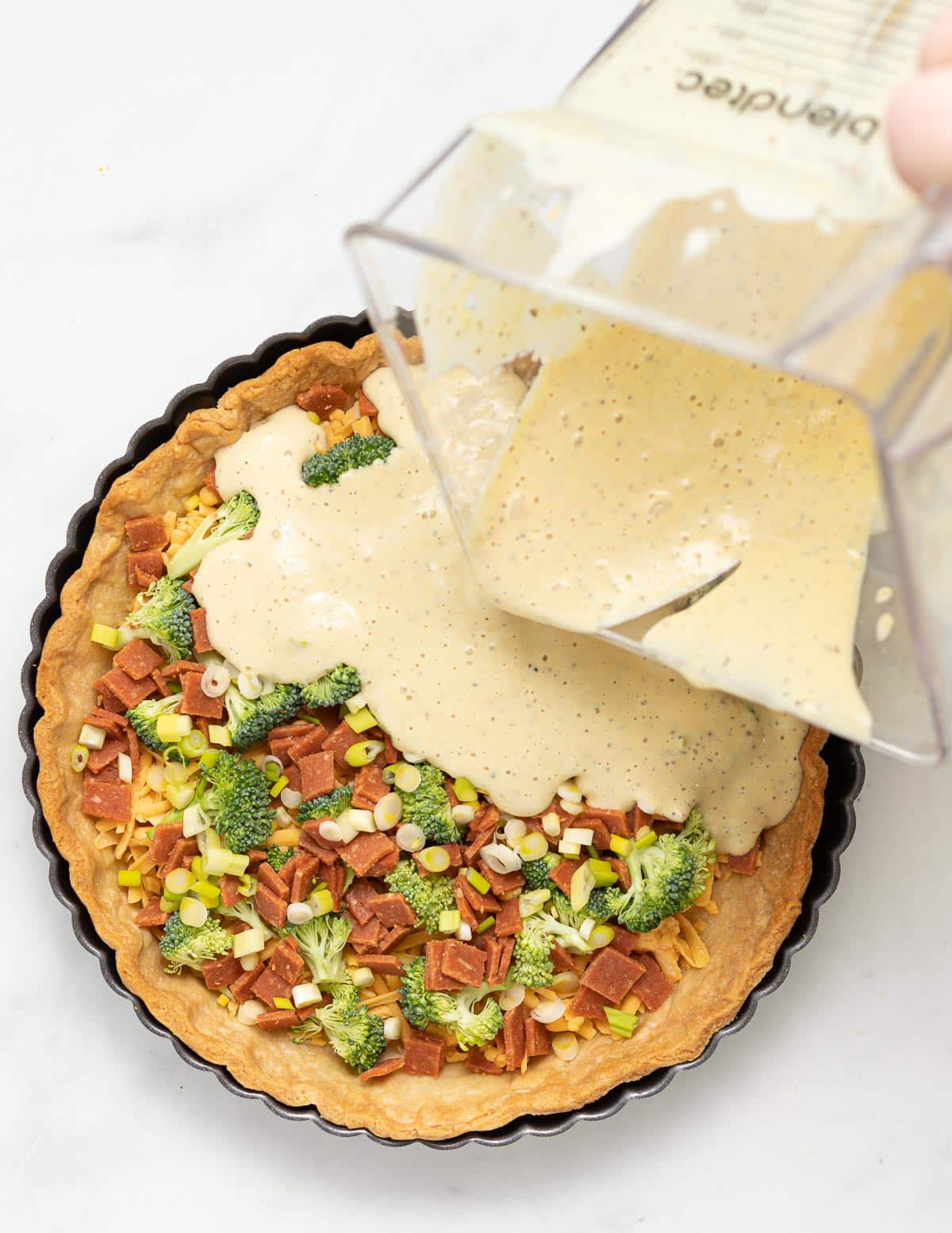 filling being poured into a quiche