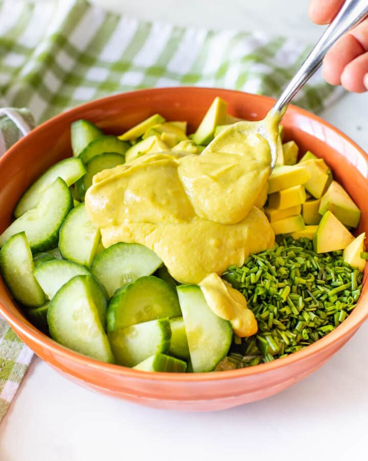 vegan avocado dressing being spooned onto a salad