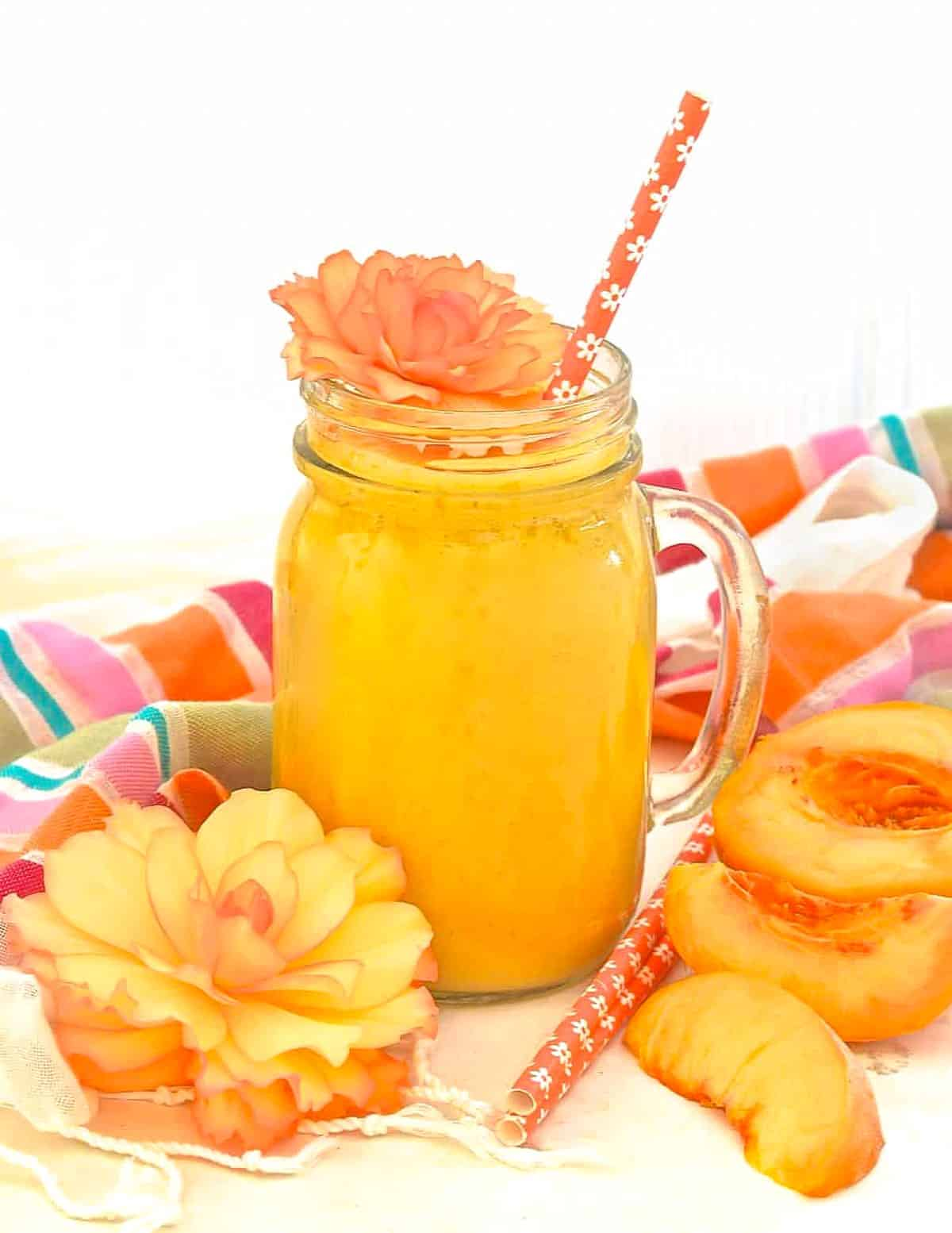 a peach smoothie with a straw