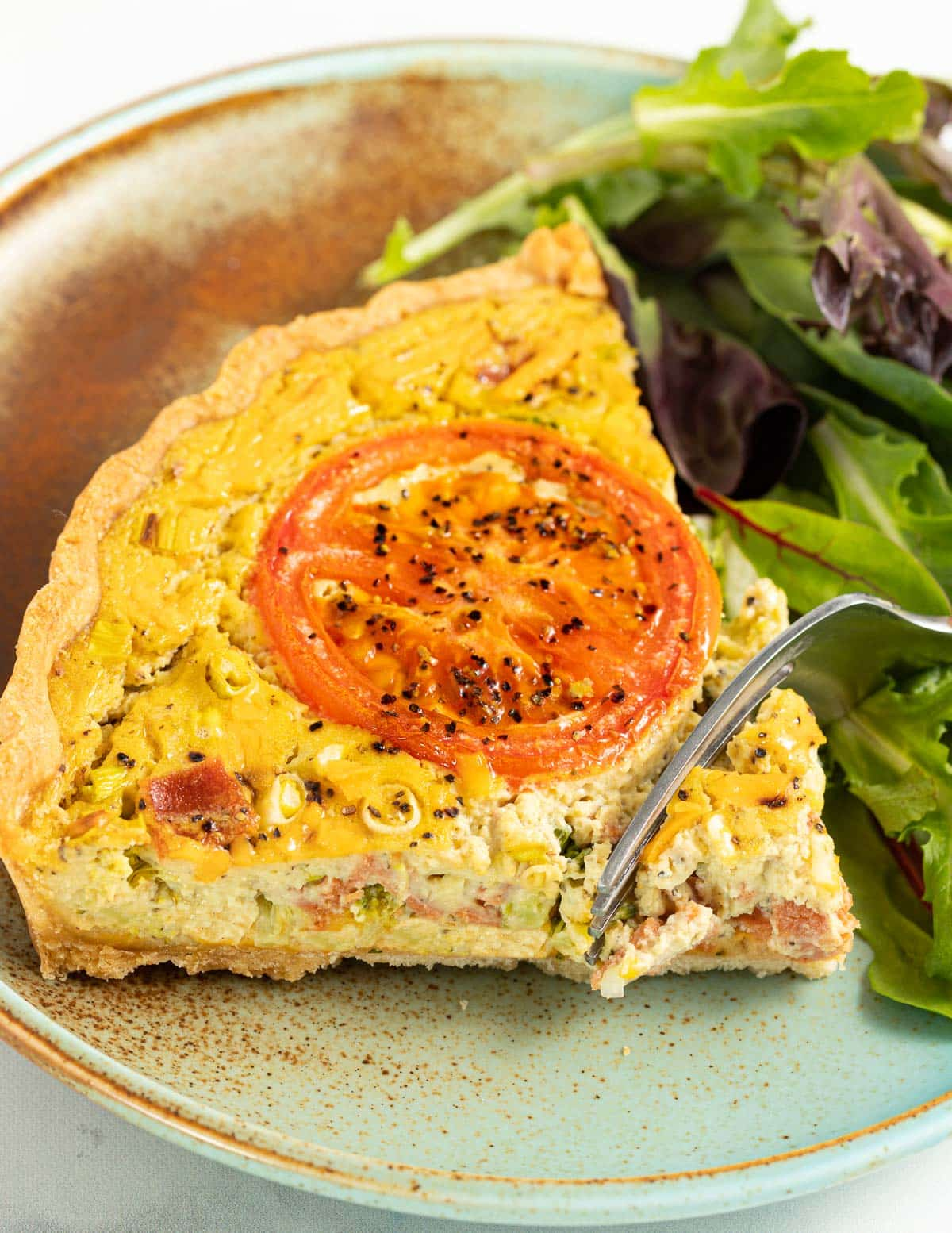 a fork cutting into a piece of quiche