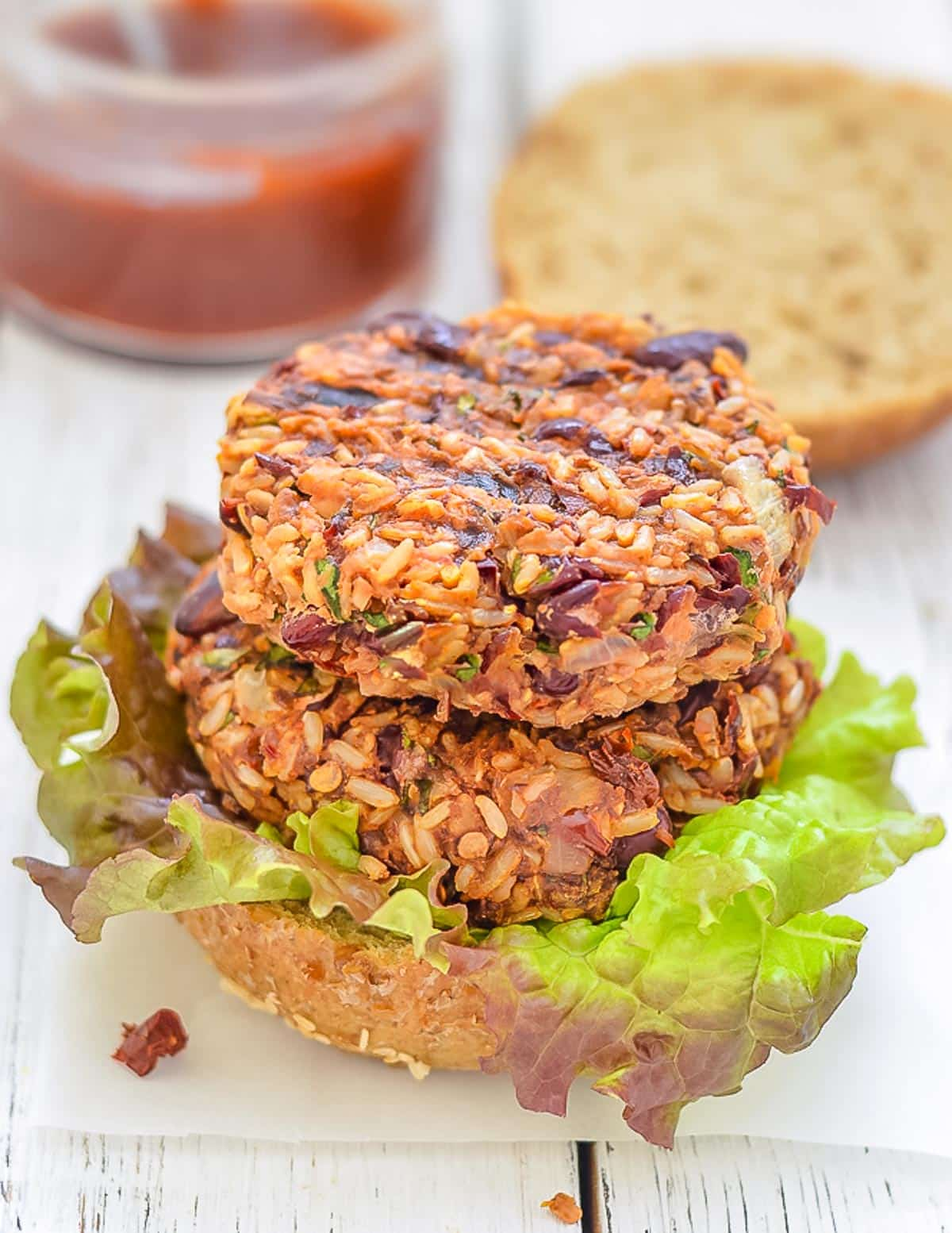 2 red bean and rice burgers stacked on a bun
