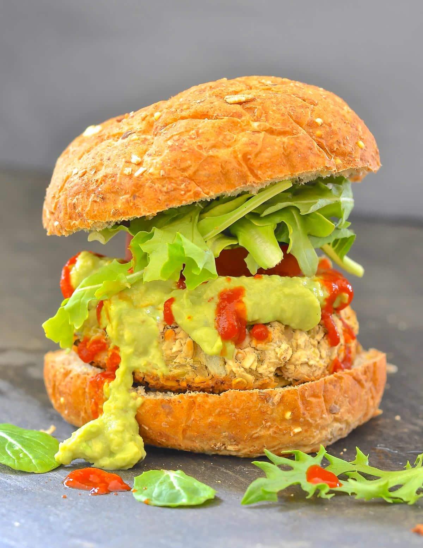a white bean artichoke burger in a bun with guacamole and hot sauce