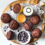 muffins on a wooden board with a bottle of plant milk, espresso and chocolate chips