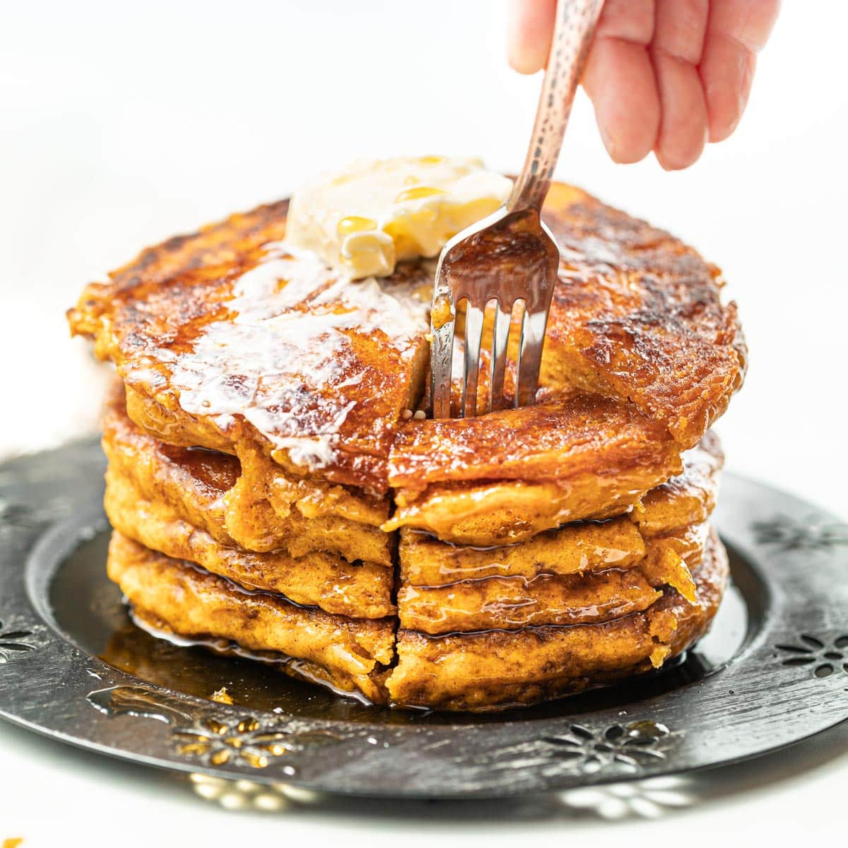 a fork going into a stack of vegan pumpkin pancakes