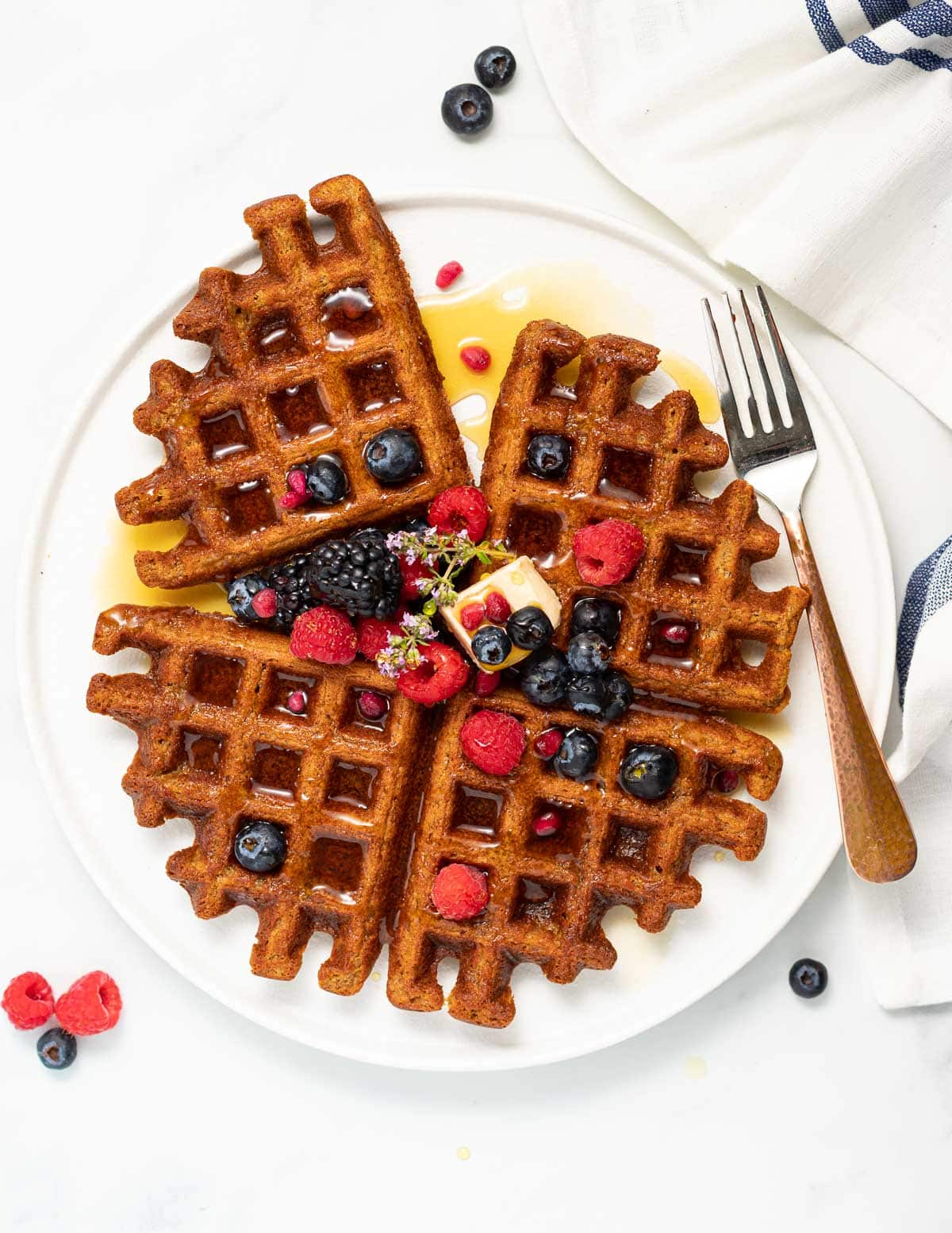 a white plate with oatmeal waffles, berries and maple syrup